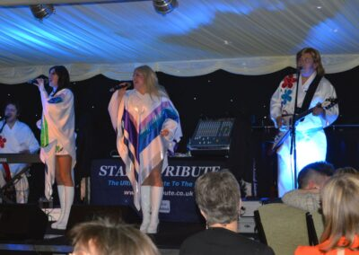 Four tribute band members singing an Abba song together