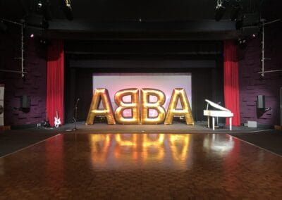 ABBA Rebjorn big gold lettering next to a white piano ready for playing